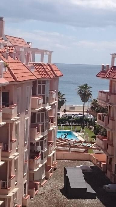 Piso en recinto cerrado con piscina en primera línea de playa. Vistas de la playa y de la piscina desde la terraza del piso.