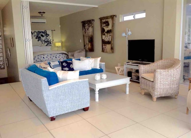 Sofa area with TV and main bedroom behind it,with a fabulous sea view. Main bedroom has shutters to close for privacy.