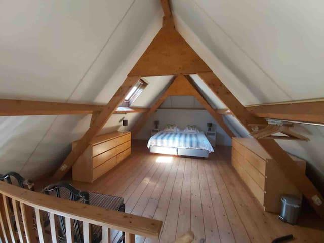 Slaapkamer met dubbel bed gezien van boven op de trap vanuit de woonkamer. Links en rechts velux ramen met verduister gordijnen. Twee grote opberg ladekasten.