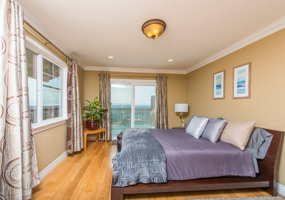 Warm master bedroom that leads directly to a large deck