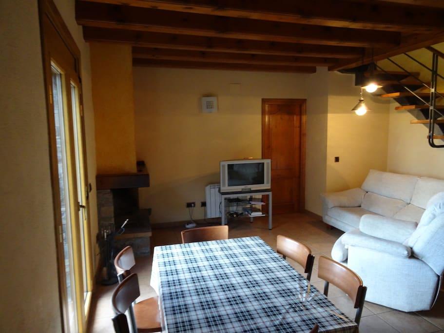 comedor sala de estar con llar de fuego y balcón con vistas.