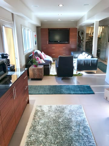 Living room with 2 large sofas & a swivel chair. RokuTV with cable