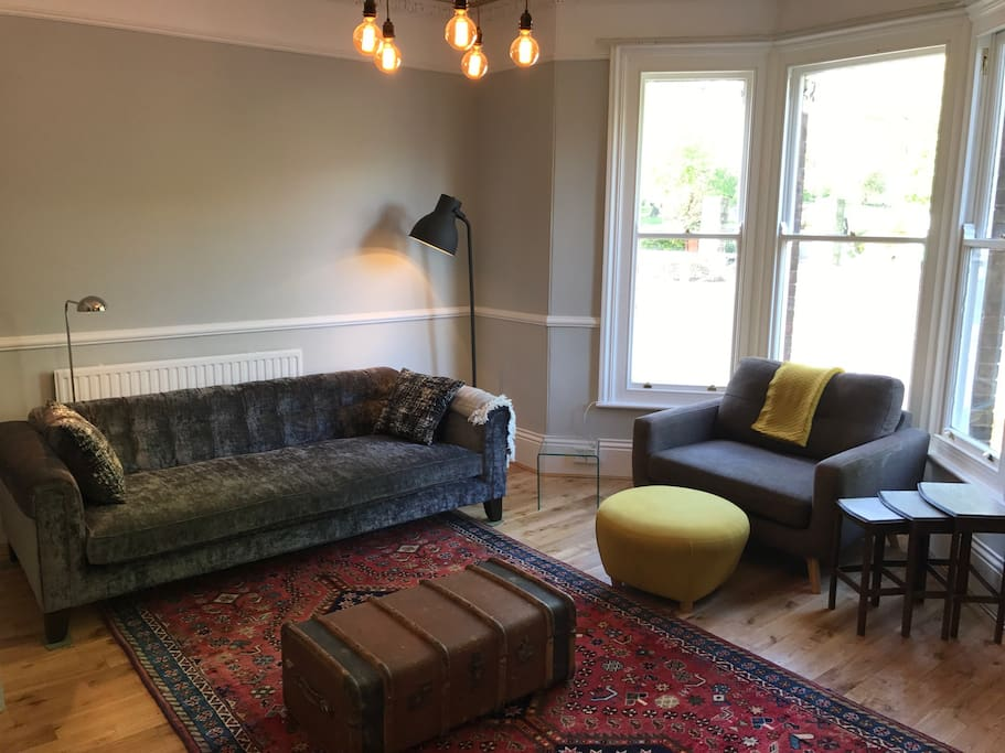 Large living room with ornate cornices, bay window, large 4 seater sofa, modern loveseat and designer centre light. The look is an eclectic mix of modern and vintage.