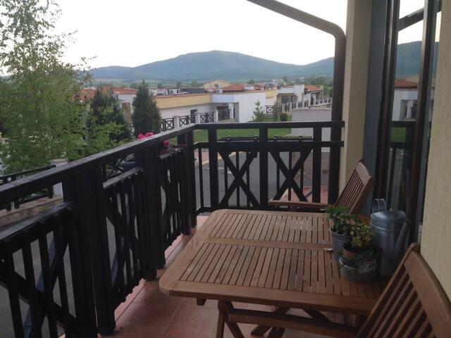 Просторный балкон с мебелью и навесом, на котором можно устраивать барбекю в пасмурную погоду.