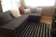 Living room sofa pulls out into a full bed (grab the loops and pull)