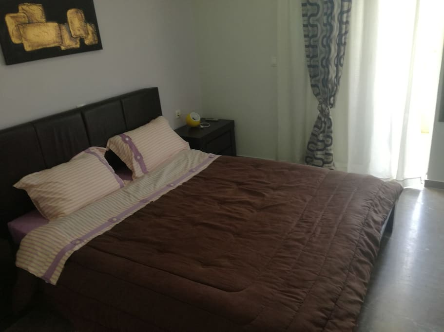 Διπλό κρεβάτι υπνοδωματίου με δύο κομοδίνα.