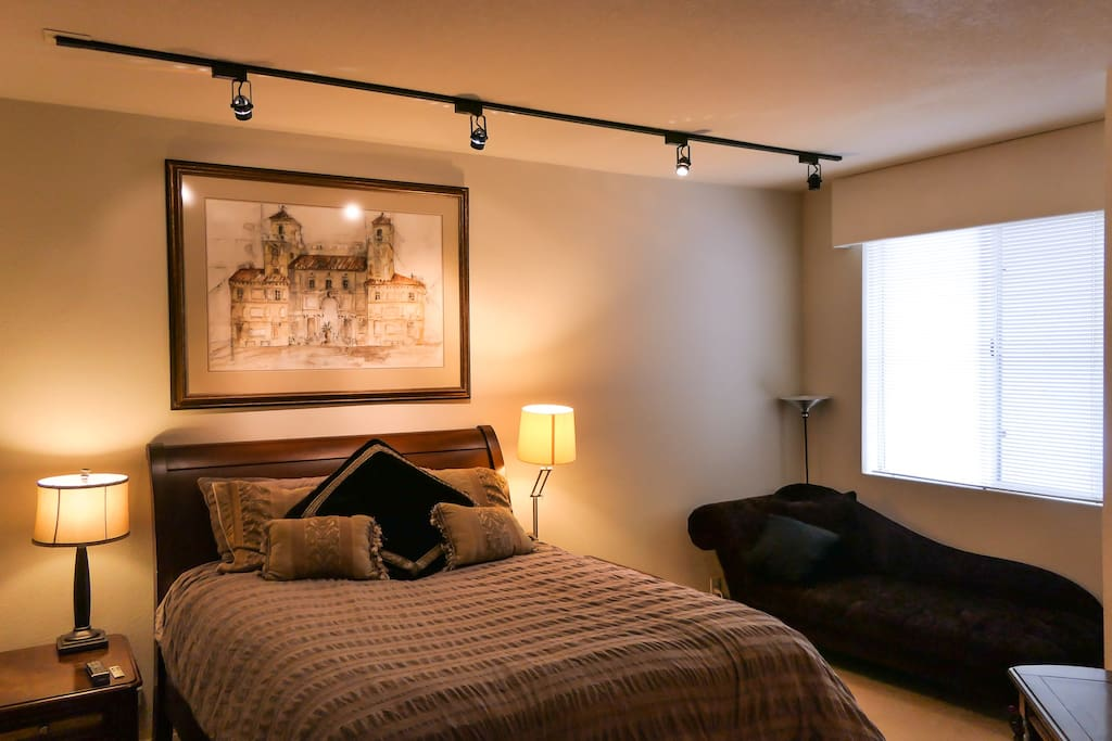 Comfortable & Relaxing Master Bedroom with track lighting & a lounging chair