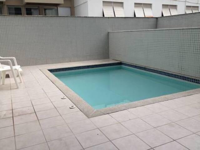 Pequena piscina com área externa compartilhada