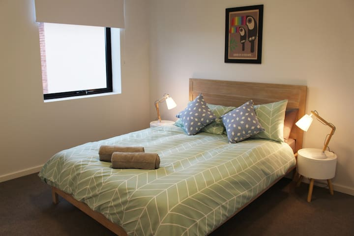Master bedroom with queen size bed, blockout blinds and large wardrobe.