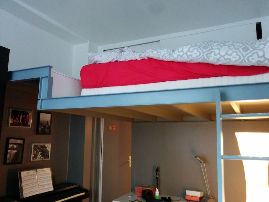 The bed is on a mezzanine in a separate room