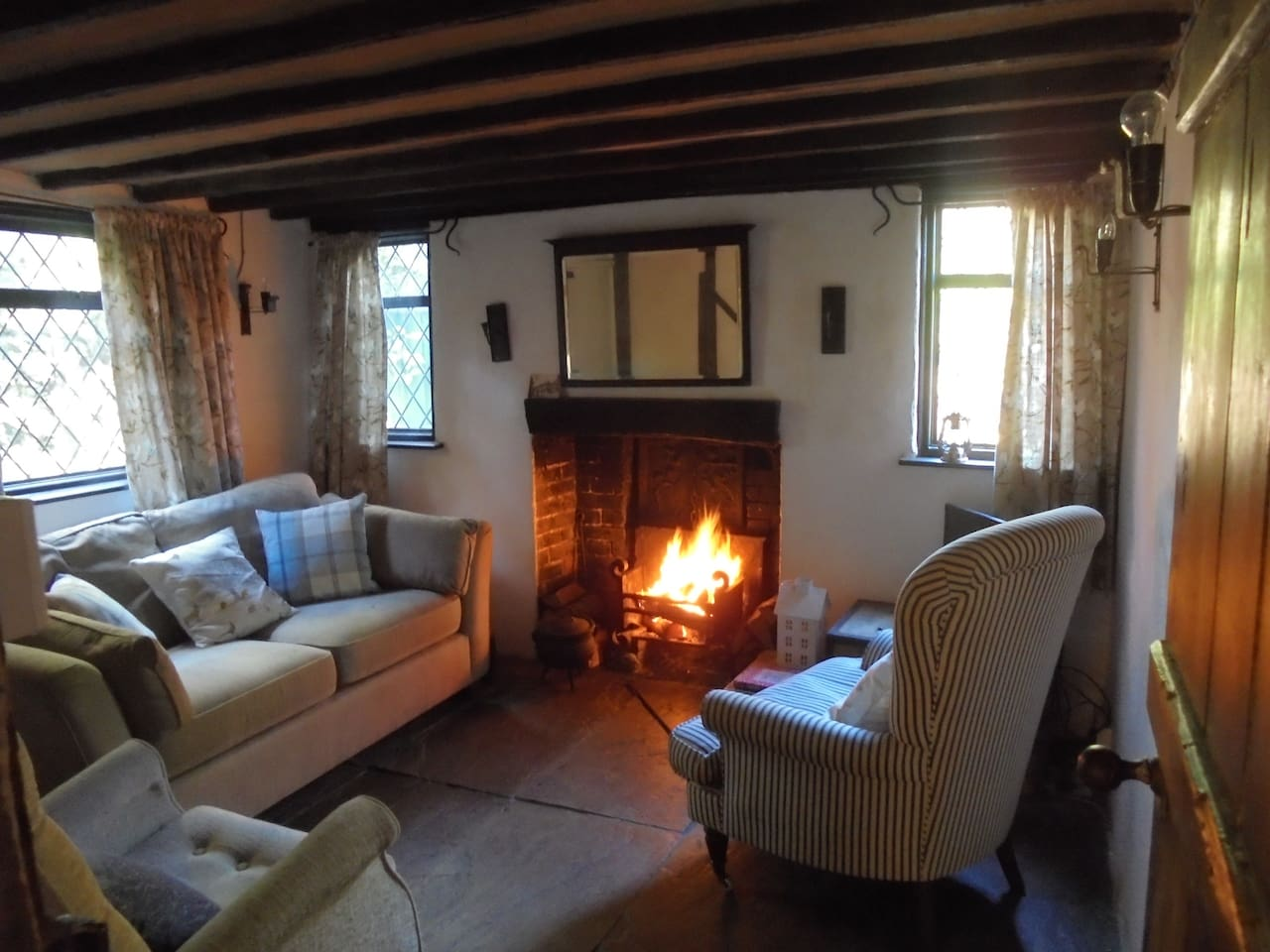 Cosy sitting room with open fireplace, flag stone floors and lime washed walls