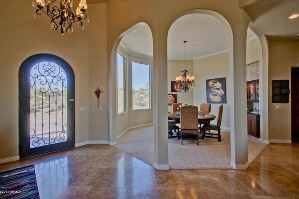 Great entry door, high ceiling and travertine stone flooring