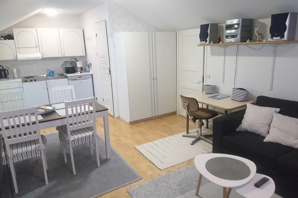 Kitchen contains refrigerator with small freezer box, dishwasher, stove, coffee maker, toaster, electric kettle and full dinner sets