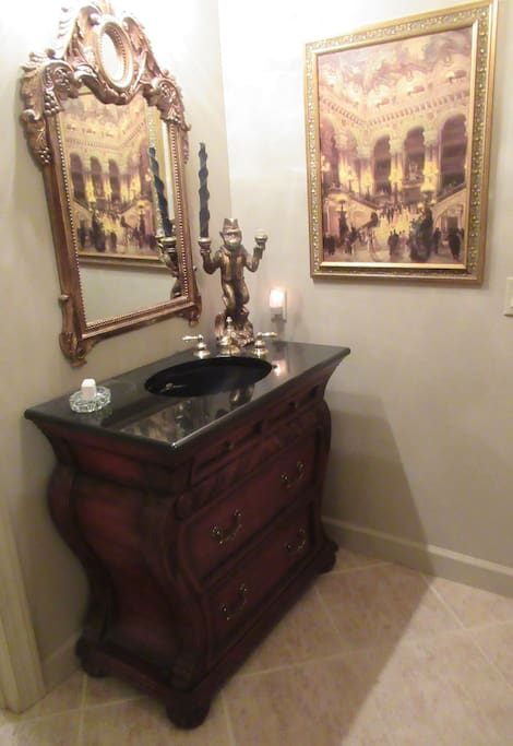 Granite counter top, gold frame mirror, crystal chandlier, shower.