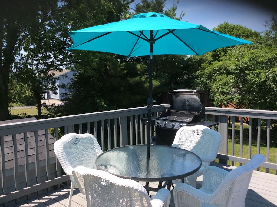 Back deck. Patio table with chairs and umbrella. Grill.