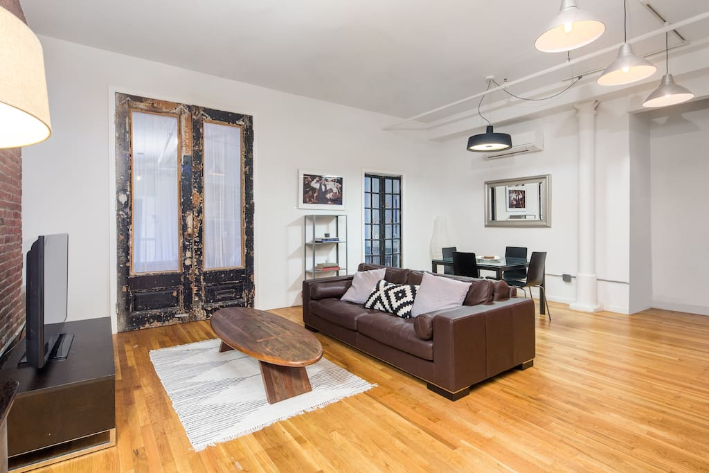 Comfortable living room with wooden floor and adjacent kitchen table.