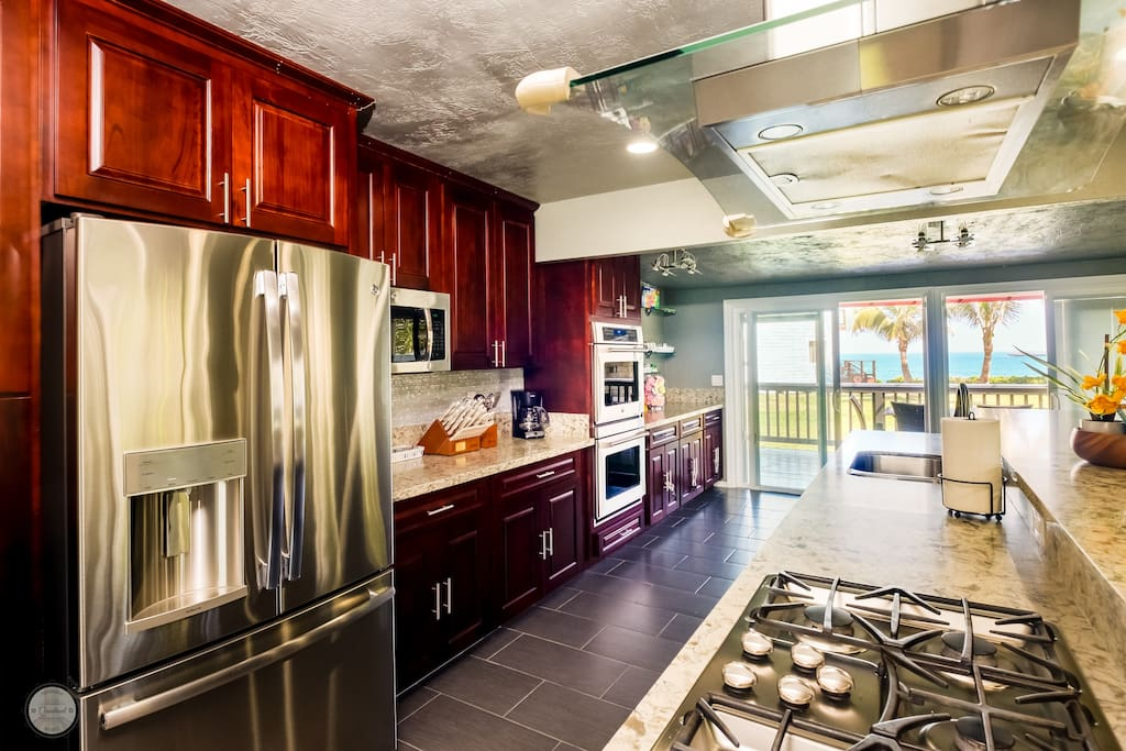 Open gas range on a 15 foot quartz island with overhead ventilation.