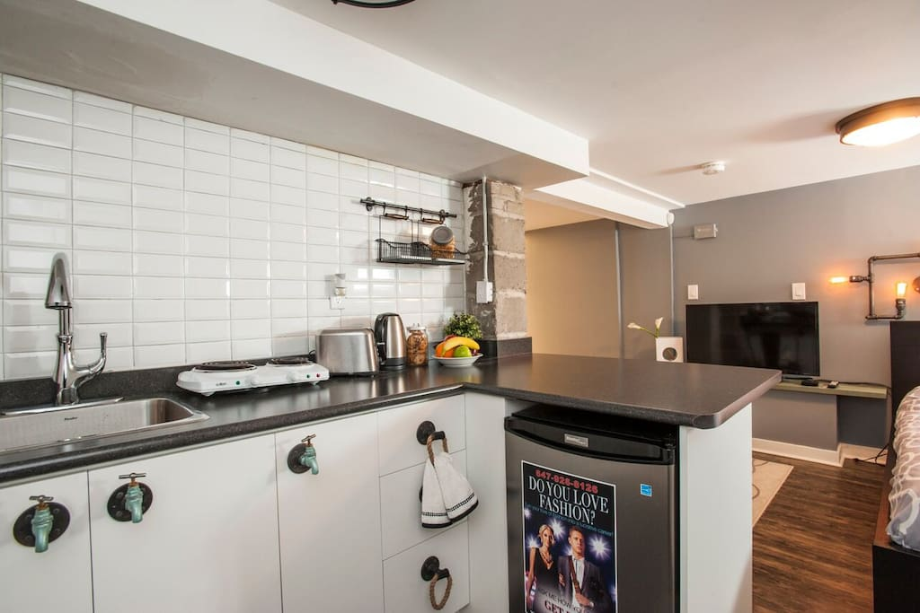 open kitchen with bar fridge, double burner, electric kettle.