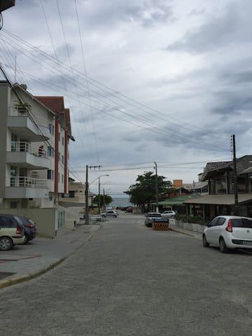 Visão da rua, com restaurante na esquina e praia ao fundo