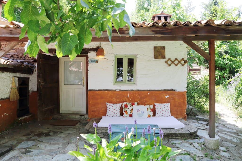 A patio with a classic Turkish sitting place that transforms to an open-air bed on hot summer nights. See the little pond right in front of the house.