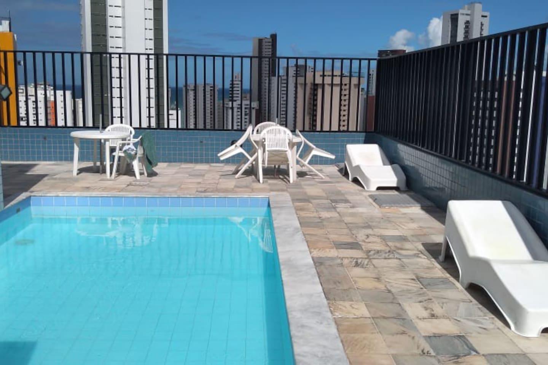 Piscina na cobertura com ducha, sauna, mesas, cadeiras, espreguiçadeiras, amplo espaço pra banho de sol, banheiros e linda vista de todo bairro de Boa Viagem.