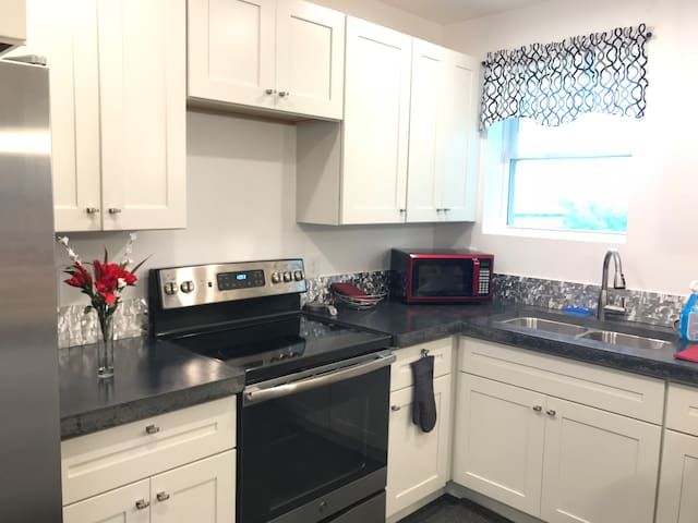 Bright and cheerful kitchen with a modern concrete countertop! Lots of room to cook or socialize!