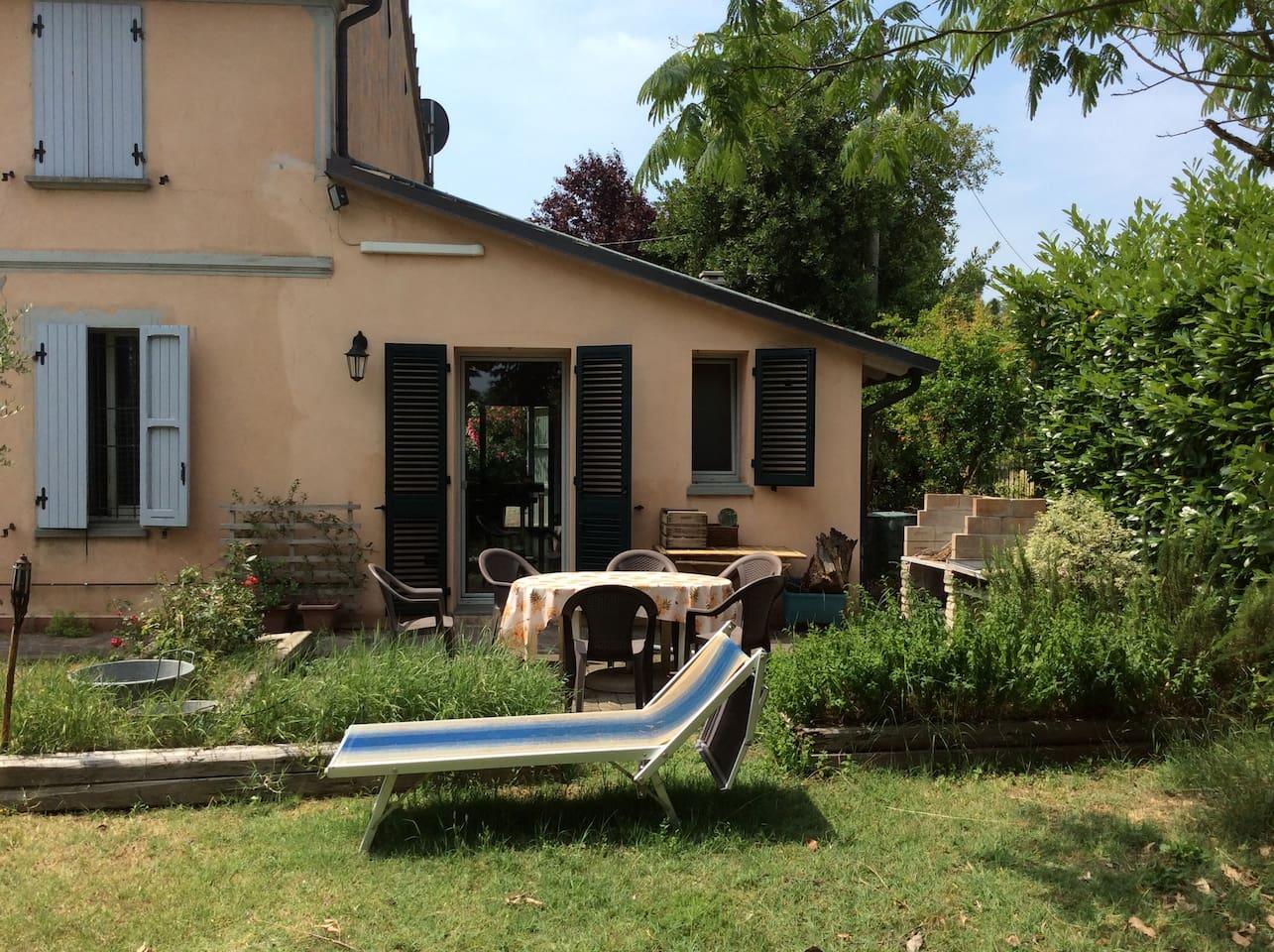 Giardino con tavolo , sedie e barbecue.