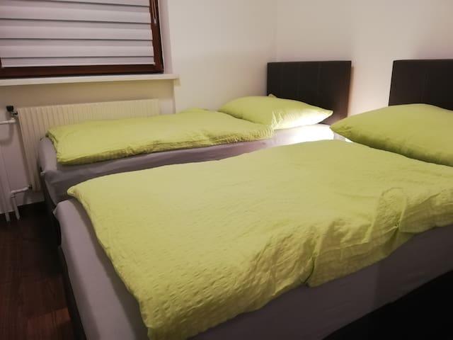 Kleineres Schlafzimmer mit 2 Boxspringbetten, die zu einem großen KingSize-Bett zusammengeschoben werden können.
