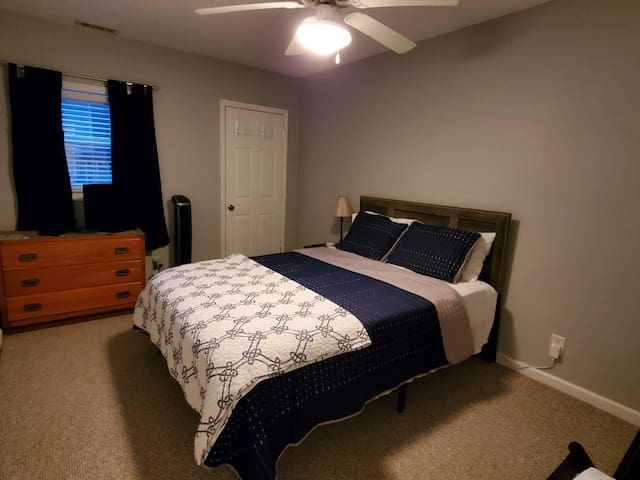 Bedroom (downstairs)  features a queen bed, closet, television+roku, luggage rack and chest of drawers