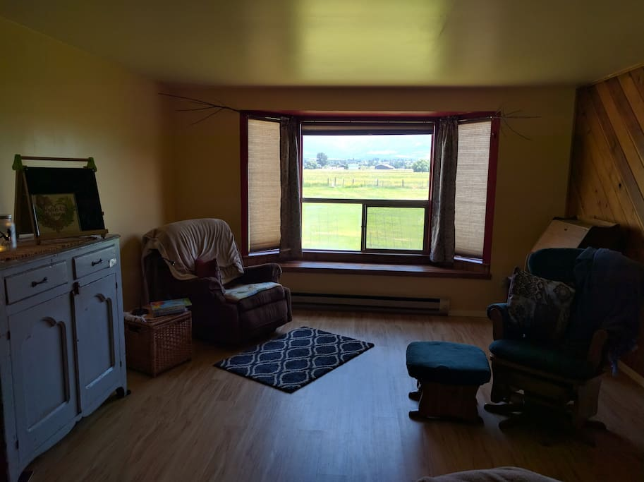 Private living room and work area with a bay window view of farmland and the Sapphire mountains