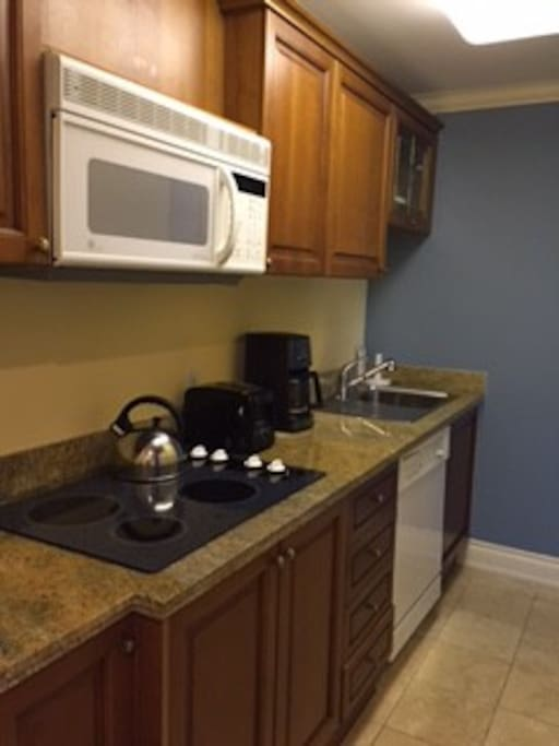 Fully appointed kitchen with utensils and refrigerator.