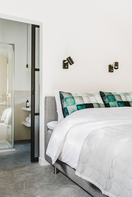 Een heerlijk bed met dubbele kussens en verstelbare en dimbare bedlampen.