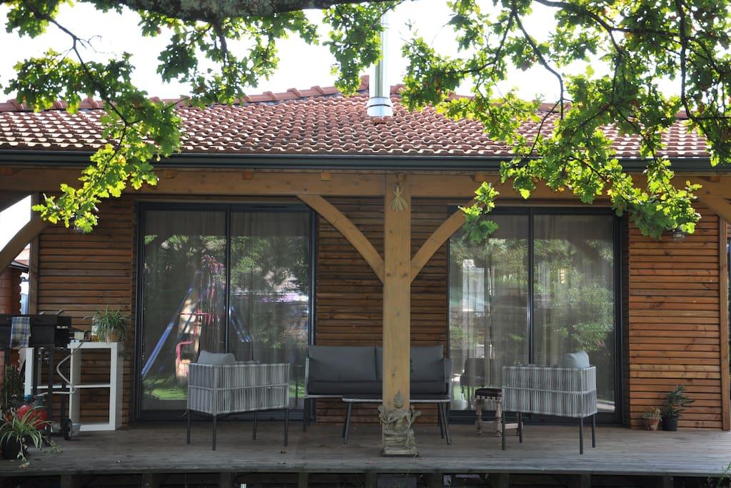 Terrasse sous porche avec plancha, salon de jardin.