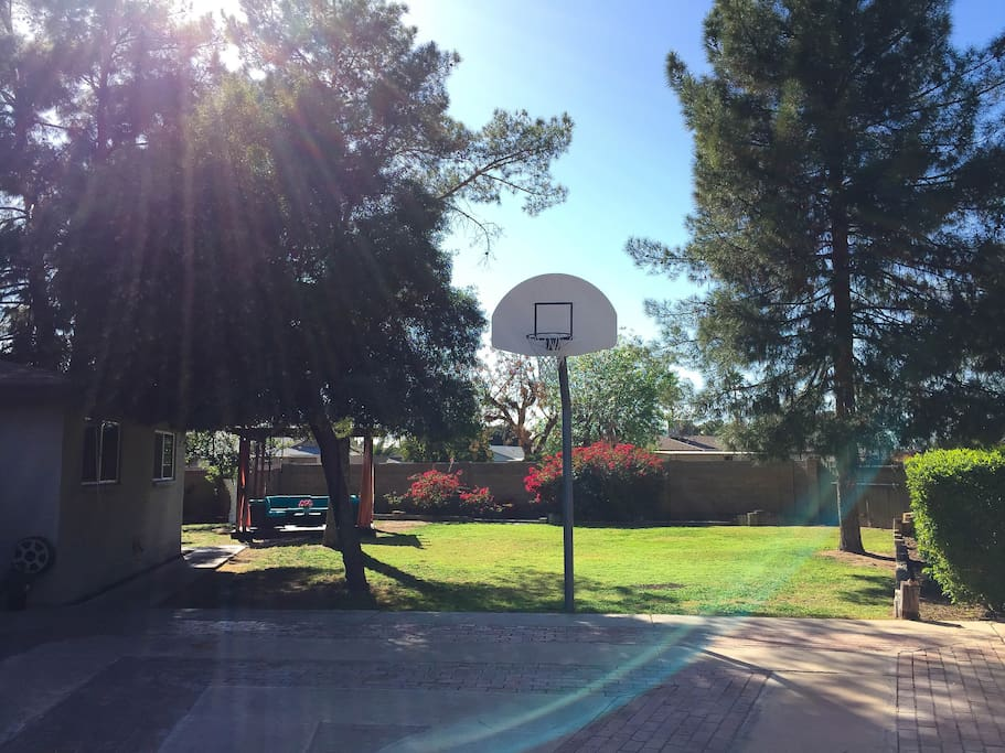 Large backyard includes half-court basketball court and gazebo among the trees.