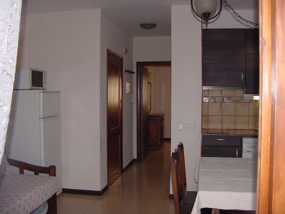 Preliminary picture of the apartment on the ground floor of a two story row house complex. The terrace and sea view is opposite this picture and here you see parts of the kitchen living room with beds and the bathroom and private bedroom further inside.