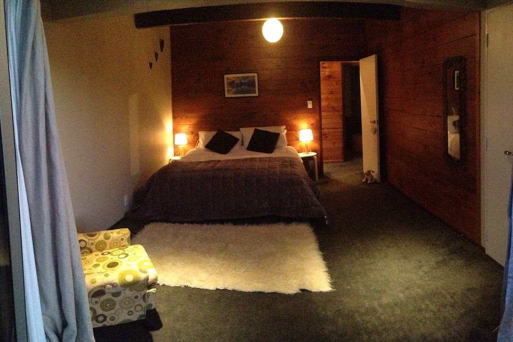 Master bedroom with King size bed and doors opening straight out onto a sunny deck