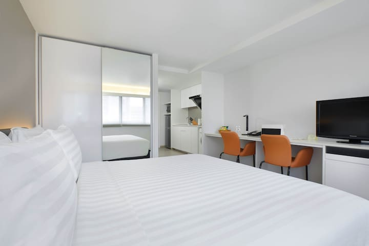 Cosy and airy studio apartment with King-sized Bed for 2. Brightly lit apartment with study/work desk, television and kitchenette.