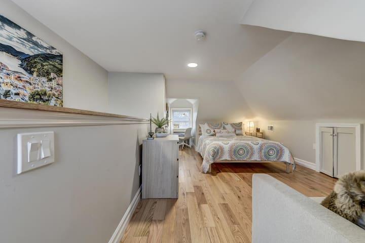 Top floor, loft-style bedroom with a queen sized bed, dresser, nightstand, work area, and half bathroom.