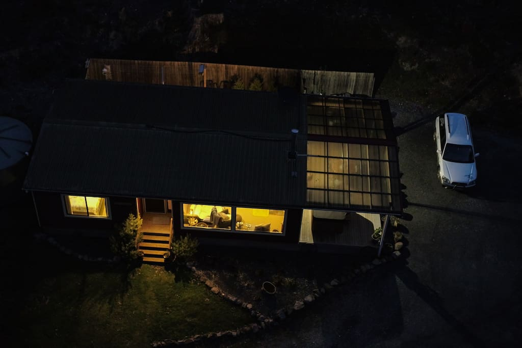 Night time photo from above of the Cottage highlighting the large windows, deck and spa area, fenced backyard and large parking area.