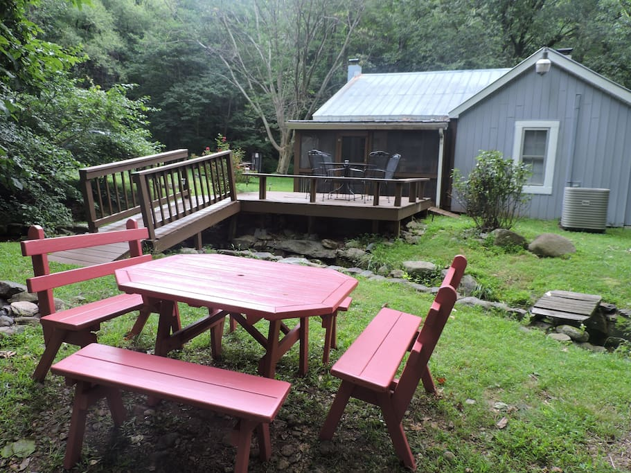 Sceened Porch off the kitchen with deck and bridge leading to fire pit and Harpers Creek.