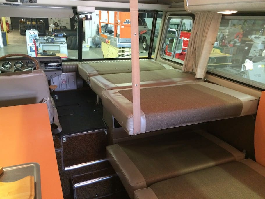 A large bunk, same size as the top, is cantilevered under the bottom. The orange formica kitchen table folds up and locks vertically. The Cortez can accommodate two adult couples / four adults.