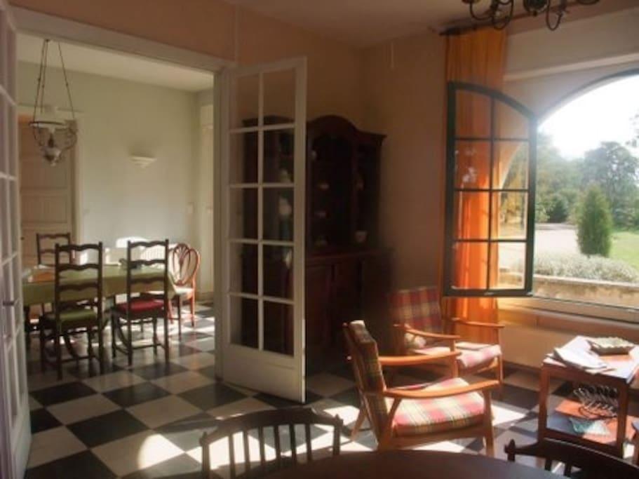 La salle à manger au fond, le salon devant, vue sur le jardin.