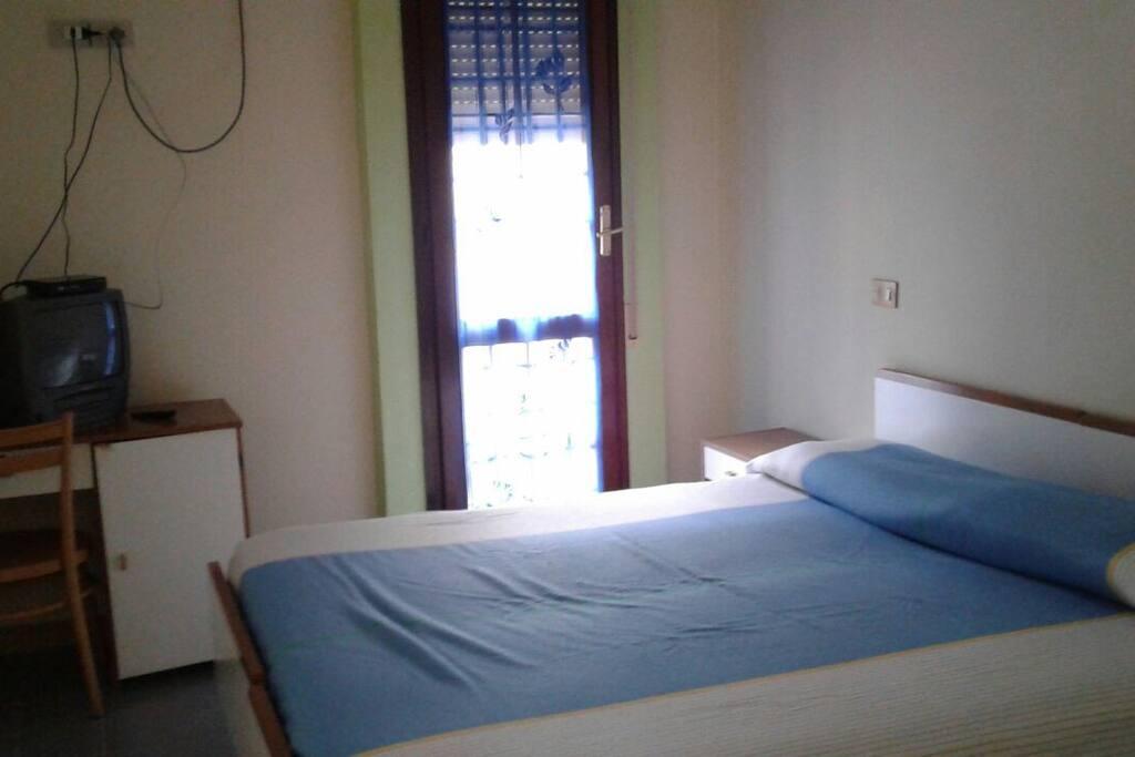 camera da letto matrimoniale con scrivania, armadio, tv e aria condizionata.