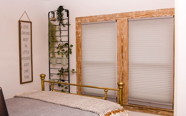 Cozy master bedroom with classic brass bed and blinds that go from sheer to full blackout!