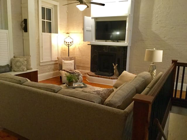 """Living room view from top of stair of private entry. Window seat to the left, hidden 55"""" smart TV, fire place, corner chaise lounge and plush couch to completely relax and unwind"""