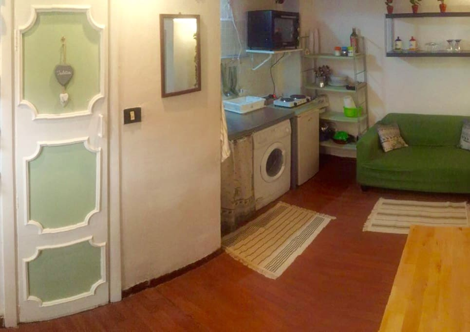 On the left: toilet with shower, kitchen corner and couch.