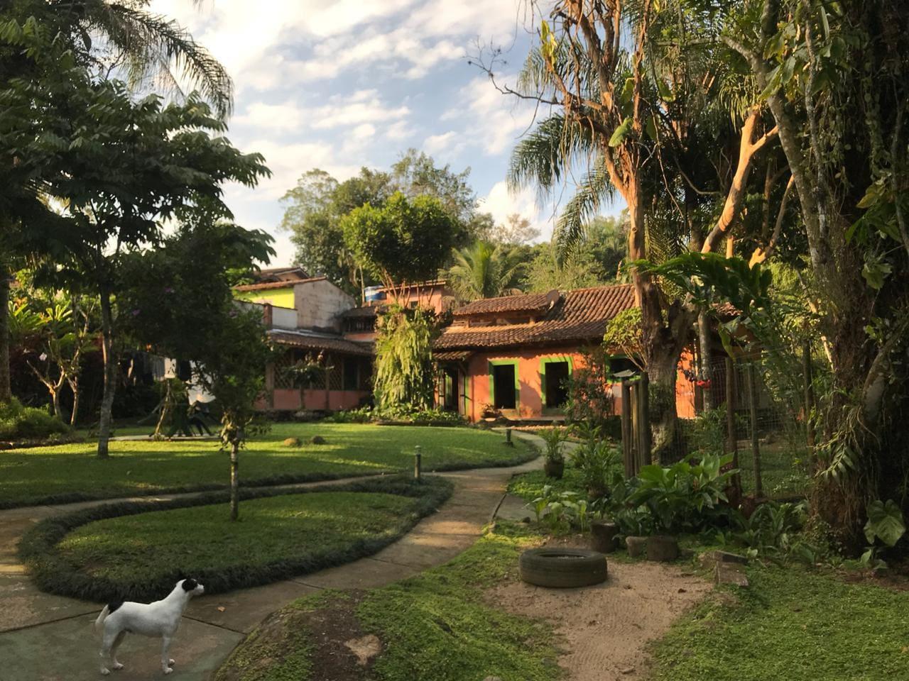 Casa com amplo jardim e cachoeira