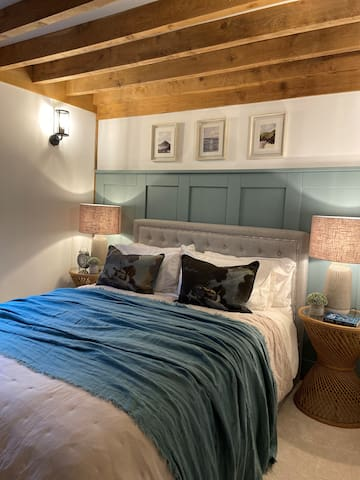 Bedroom 3 has a king size upholstered bed with a beautiful colour palette for a restful night sleep