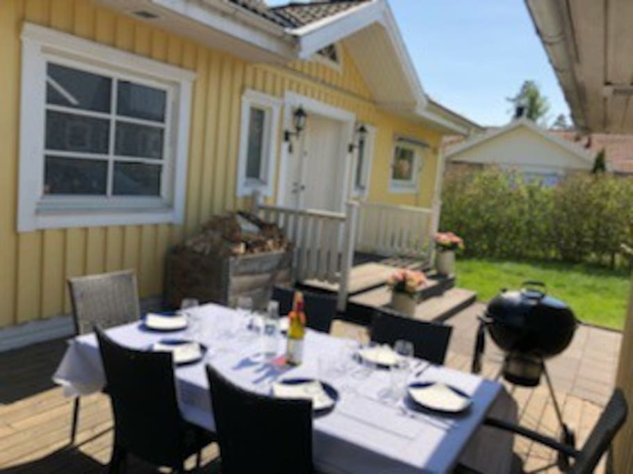 Patio at the front with table, chairs and barbecue. Uteplats på framsidan med bord, stolar och grill.
