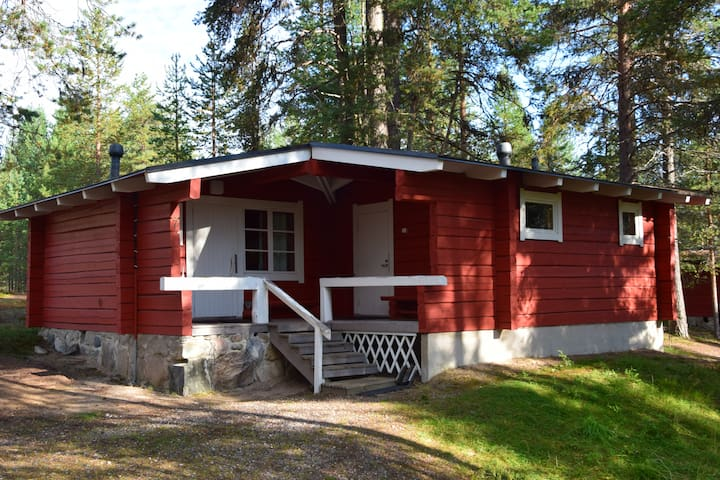 Red log cabin by the lake